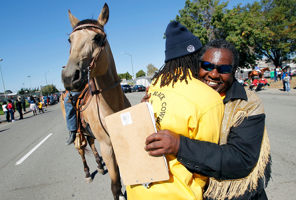 . Oakland Black Cowboy Association member Elijah McAlister, left, gets a hug from parade coordinator Henry Linzie during the 39th annual Oakland Black Cowboy Parade and Heritage Festival in Oakland, Calif., on Saturday, Oct. 5, 2013. The event also featured food, entertainment and pony rides for kids at De Fremery Park. The OBCA began in 1975 and educates the public about the role that black cowboys played in history and building of the west. McAlister is the grandson of OBCA president Wilbert McAlister. (Jane Tyska//Bay Area News Group)