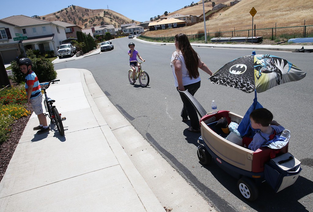 . Kristi Ouimet pulls her son Matthew Ouimet, 3, as they head back from a local park with Matthew\'s brother Patrick, 9, left, and sister Molly, 11, center, in Antioch, Calif., on Friday, May 23, 2014. (Jane Tyska/Bay Area News Group)