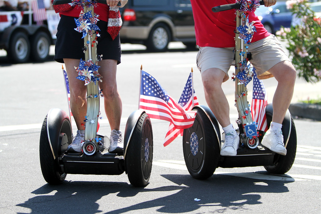 . Gennie Backes, left, and Jeff Backes of the Solid Gold Segway Dancers warm up for the start of Redwood City\'s 75th annual Fourth of July Parade on Thursday, July 4, 2013. (Kirstina Sangsahachart/ Daily News)