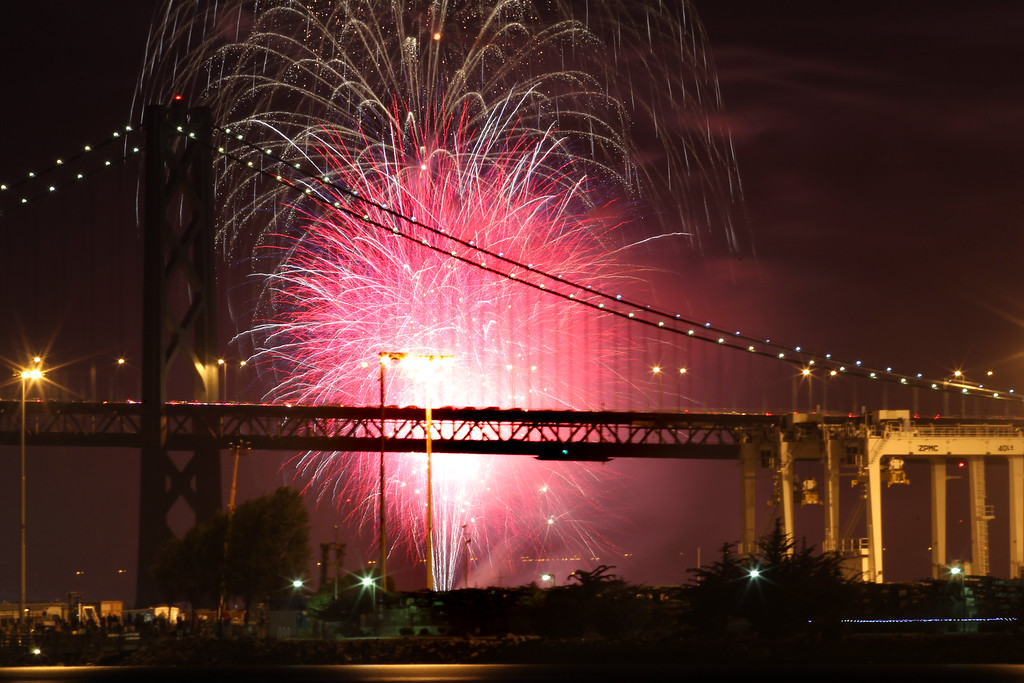 . Fireworks light up the sky and the Bay Bridge to conclude the Independence Day celebrations seen from Middle Harbor Shoreline Park in Oakland, Calif., on Thursday, July 4, 2013.  (Ray Chavez/Bay Area News Group)