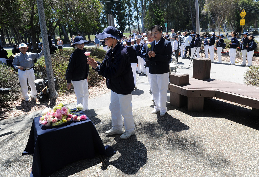 . Volunteers of the Tzu Chi Foundation make an offering of flowers following a prayer ceremony for the Asiana Flight victims put on by the Tzu Chi Foundation in Burlingame, Calif., on Saturday, July 13, 2013. Tzu Chi is an international Buddhist relief organization that began in Taiwan and offers compassionate efforts for charity, medical treatment, education and disaster relief.  (Dan Honda/Bay Area News Group)