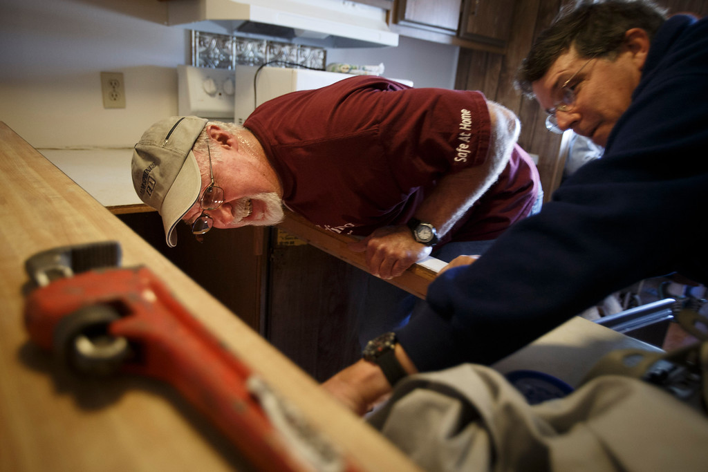 . Volunteers from Rebuilding Together Silicon Valley Mike Aro, left, and Brian Carter, right, work on replacing a kitchen sink at Maria Januzys\' mobile home on Jan. 21, 2013 in Morgan HIll. The volunteers worked on various fixes including replacing the countertop and sink, replacing her front steps, installing shelving, and more. (Dai Sugano/Staff)