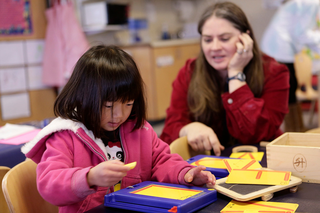 . Akemi Honma, 4, works on an activity with the help of her teacher, Rachel Martensson, at the Mountain View Parent Nursery School in Mountain View, Calif. on Friday, Feb. 8, 2013. The Mountain View-Whisman School District has decided that if parents hold back an eligible child from kindergarten, it will help evaluate those children for kindergarten-readiness the following year. Some will be sent to first grade rather than kindergarten. (Gary Reyes/ Staff)
