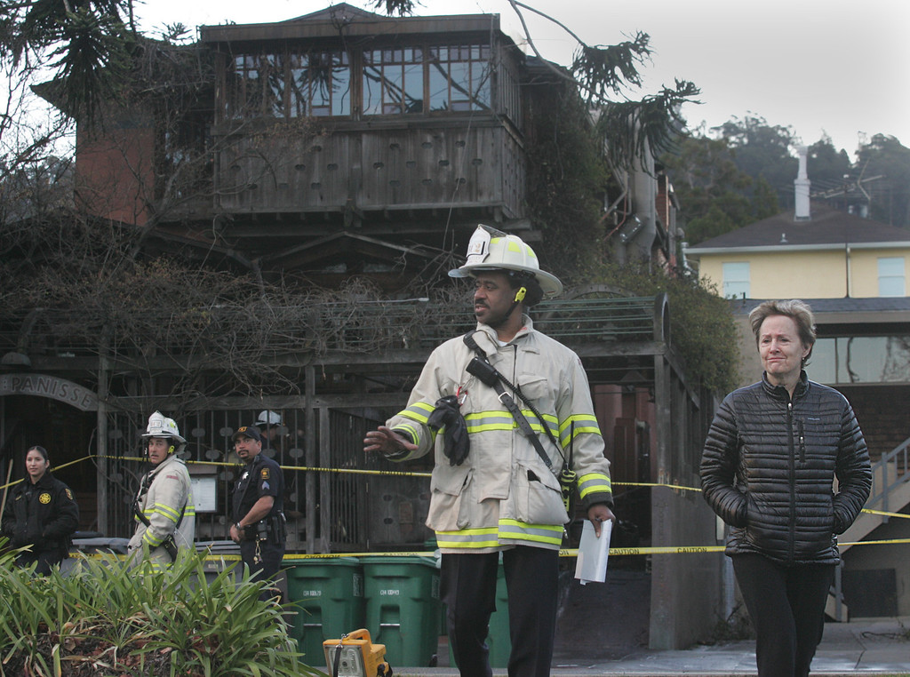 . Alice Waters, at right, owner and executive chef of world famous Chez Panisse restaurant in Berkeley finishes a tour of her fire damaged restaurant on Friday March 8, 2013. At left is Berkeley\'s Acting Deputy Fire Cheif Avery Webb. Officials are calling the fire, which started under the front porch, suspicious. (Doug Oakley/Staff)