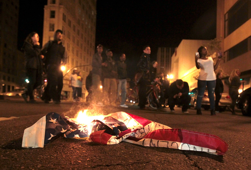 . An American flag burns along Broadway near Telegraph Avenue during a protest march in Oakland, Calif., early Sunday July 14, 2013. Protesters marched through the city with some in the group smashing windows, spraying graffiti and setting fires after learning that George Zimmerman had been found not guilty in the shooting death of Trayvon Martin. (Anda Chu/Bay Area News Group)