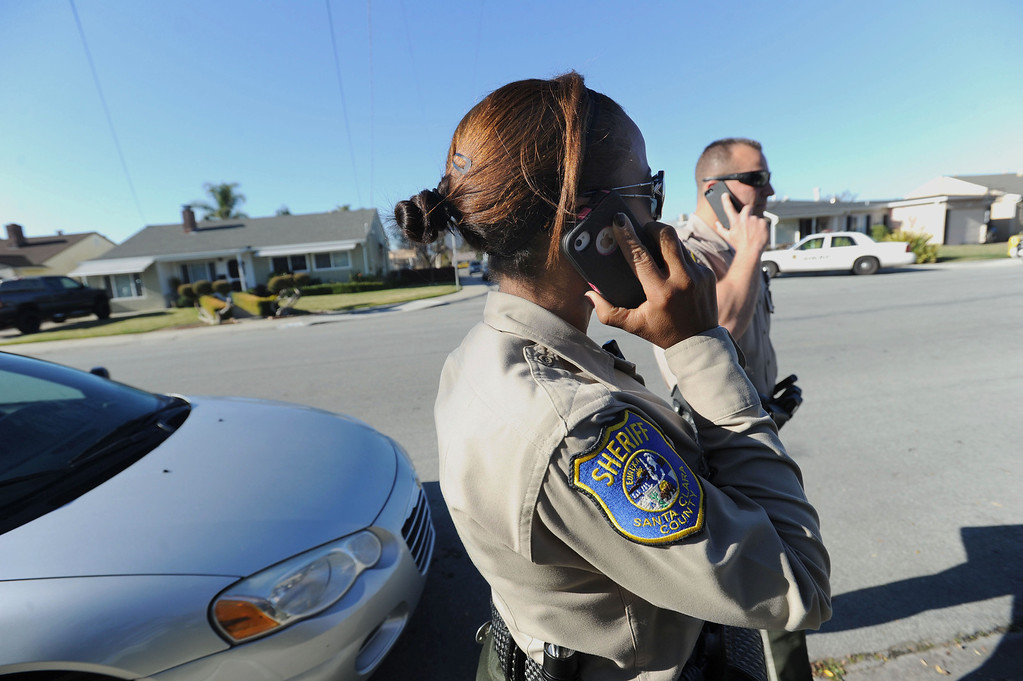 . Santa Clara County Sheriff\'s deputies Ryan Griep, right, and Dessaure (she did not want her first name used), left, try to get verification of some information after visiting a home in an unincorporated portion of East San Jose, Calif. on Monday, Feb. 11, 2013. The Santa Clara County Sheriff\'s Office is increasing its efforts to take once lawfully owned firearms from those who can no longer own them due to more recent circumstances in their lives. Officers are attempting to make contact with these people to ask them to voluntarily turn over any firearms. A monthly list of these people is put out by the Department of Justice. (Dan Honda/Staff)