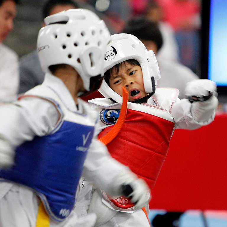 . From right, Gavin Kaenjak of Blue Dragon Tae Kwon Do kicks Redrick Sambrano of Blue Manila Tae Kwon Do at the Tet Festival Tae Kwon Do  tournament, under 5-year-old division, hosted by the Coalition of Nationalist Vietnamese Organizations of Northern California (CONVONCA) at the Santa Clara County Fairgrounds in San Jose, Calif. on Saturday, February 2, 2013.  Sambrano won the match and division.  (LiPo Ching/Staff)
