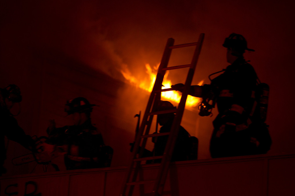 . Firefighters are silhouetted against the flames from a fire inside a vacant, wood-framed house on Harrison Street near 7th Street, Wednesday, Jan. 23, 2013 in Oakland, Calif. The building, which fire investigators said was built in 1896, caught fire when squatters inside it tried to cook food over an open flame. (D. Ross Cameron/Staff)