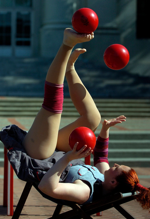 """. Circus Oz performer Hazel Bock juggles with her feet and hands as the Australian circus group performs on Sproul Plaza at the University of California to preview their new show \""""From the Ground Up\"""" in Berkeley, Calif. on Wednesday, Feb. 13, 2013. (Kristopher Skinner/Staff)"""