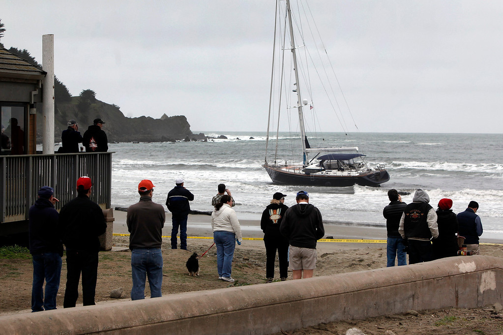 . Spectators watch as the 82-foot long sailboat named the Darling rocks in the surf after running aground off Linda Mar Beach in Pacifica, Calif., Monday morning March 4, 2013. (Karl Mondon Photo)