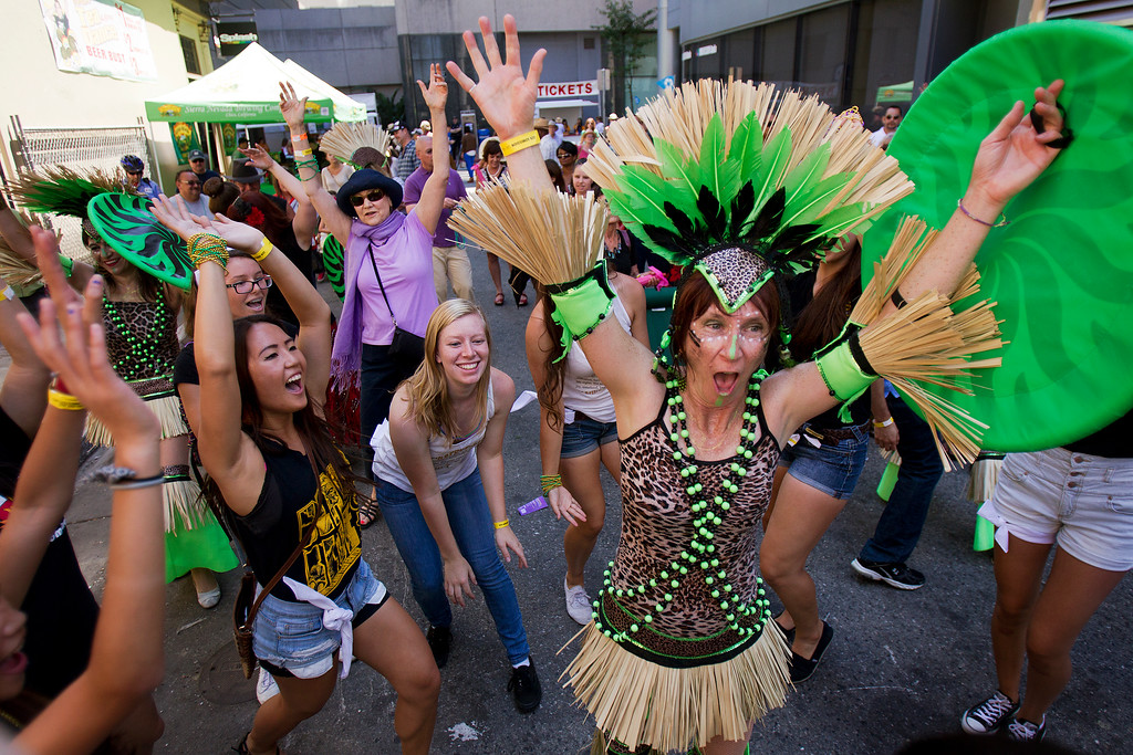 . At left, members of the Chargerettes drill team from Wilcox High School dance with the Samba Mundial group, right, at the San Jose Jazz Festival, in San Jose, Calif., on Saturday Aug. 10, 2013.  (LiPo Ching/Bay Area News Group)