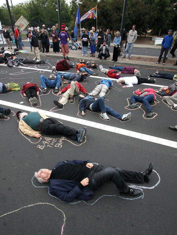 . Daniel Ellsberg lays on the street with other protestors in Livermore, Calif. on Tuesday, Aug. 6 2013. The chalk outlines represent the vaporized bodies of victims of the atomic bomb blasts in Japan. Ellsberg was  later arrested by an officer from LLNL Protective Forces at the protest at LLNL.   (Jim Stevens/Bay Area News Group)
