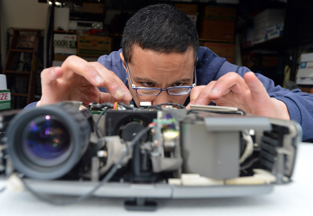 """. Peter Mui tinkers with a digital projector at his home in Berkeley, Calif. on Tuesday, Feb. 5, 2013. Mui and others run \""""Fixit Clinics,\"""" where they assist people in the repair of various electrical appliances, from televisions to toasters.(Kristopher Skinner/Staff)"""