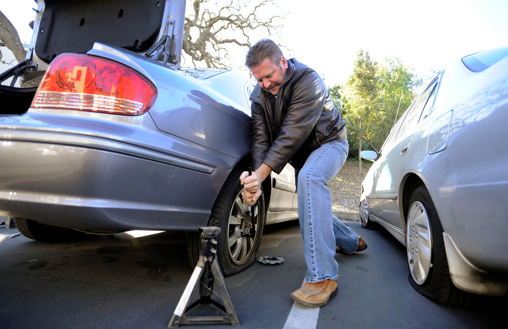 . Joe Vitale loosens stubborn lug nuts from a Hyundai with four slashed tires at an apartment complex on Bel Air Drive in Concord, Calif., on Monday, Feb. 11, 2013. Vitale was in the area working on a construction job when he stopped to help out Dan Zywicki, who was changing the tires of his daughter\'s car. Kay Zywicki noticed her four flat tires on Sunday. Other residents also had their tires slashed. (Susan Tripp Pollard/Staff)