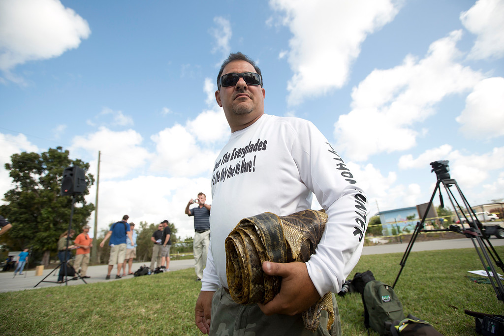 """. Trapper \""""Python Dave\"""" Leibman holds a roll of snake skins he is selling at the Python Challenge kick-off in Davie, Fla. (AP Photo/J. Pat Carter)"""