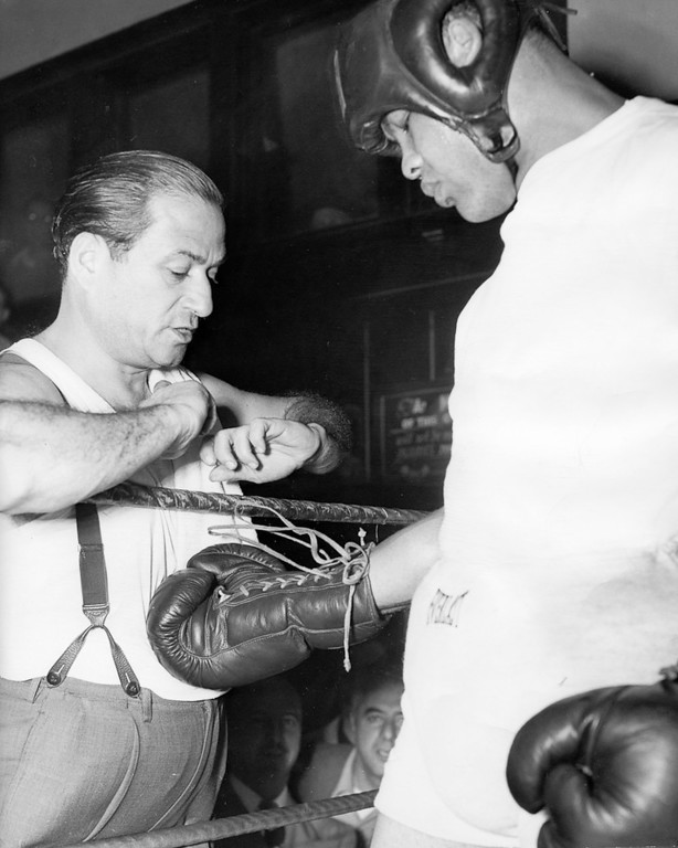 . San Francisco, December 18, 1949 - Trainer Manny Seamon checks the laces on Joe Louis\' gloves prior to a workout. (Oakland Tribune Photo)