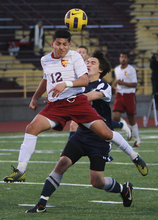 . Menlo-Atherton\'s Marcos Amaral heads the ball away from their goal  against Carlmont\'s Julian Smith during a game in the second half  at Menlo-Atherton High School in Atherton on Monday, Jan. 28, 2013.  (Kirstina Sangsahachart/ Daily News)
