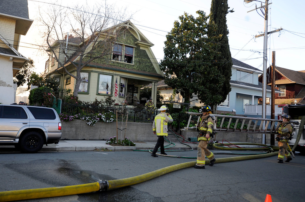 . Firefighters bring a ladder to a home in the 400 block of H Street that caught fire in the back of the second story in Antioch, Calif., on Wednesday, March 13, 2013. (Susan Tripp Pollard/Staff)