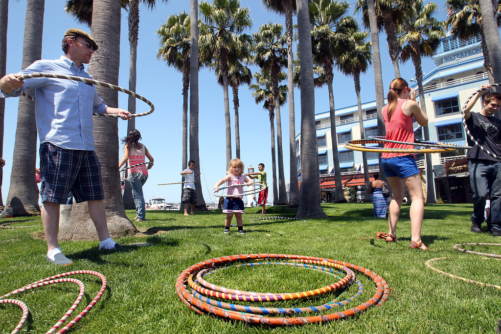 . Bill Rowley, left, and his two-year-old daughter Sinclair, of Oakland, try the hula hoop as one of the activities during the Independence Day celebration at Jack London Square in Oakland, Calif., on Thursday, July 4, 2013.  (Ray Chavez/Bay Area News Group)