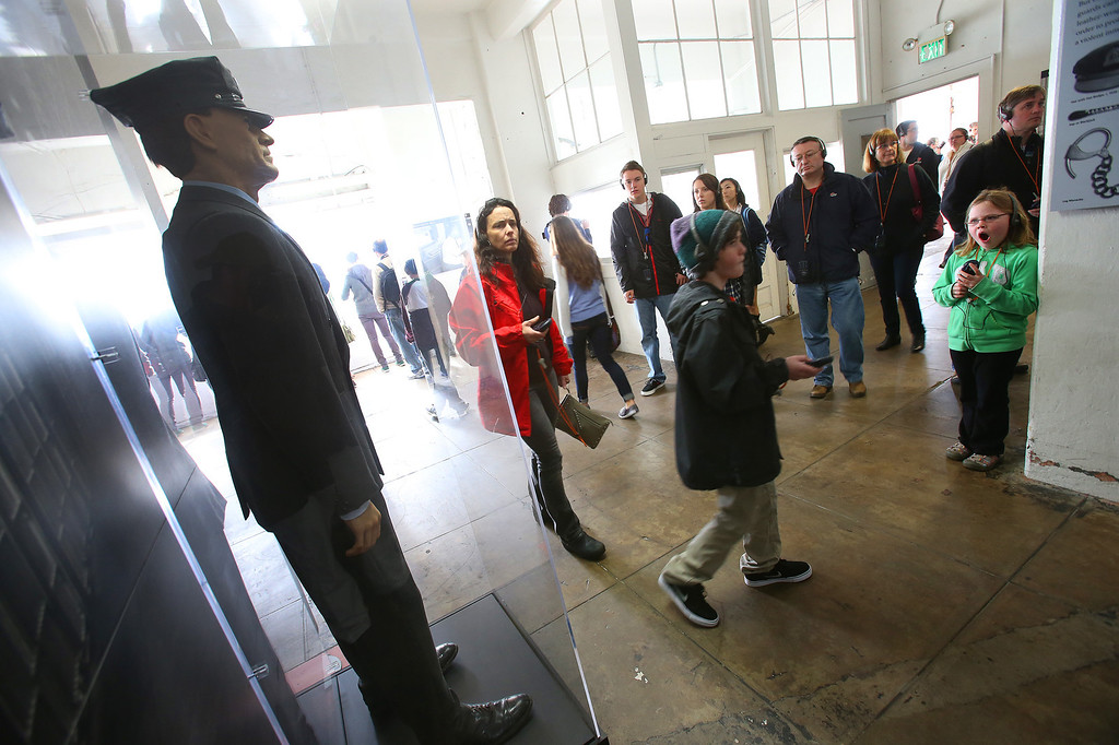 . Tourists walk past a prison guard display in the administration building of the federal penitentiary on Alcatraz Island on Monday, March 18, 2013 in San Francisco, Calif.  The federal prison on the island closed 50 years ago and is now a tourist destination.  (Aric Crabb/Staff)