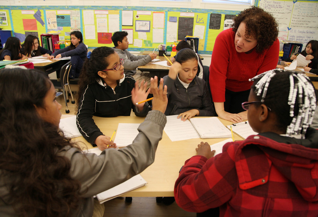 . Teacher Stephanie Perry works with students from left, Perla Rodriguez, 11, Abril Soto, 12, Ana Farias, 11, and John\'Iyah West, 11, on some 6th grade math word problems during class at Peres Elementary School in Richmond, Calif., on Friday, Feb. 8, 2013.  Peres school is one of two elementary schools in Richmond that have raised their average API test scores to over 800. (Laura A. Oda/Staff)