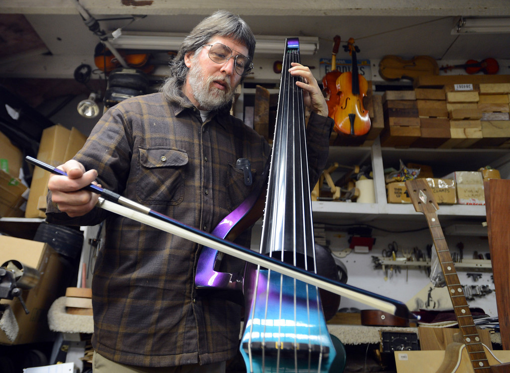 . John Jordan plays an electric upright bass he handcrafted from maple in his Concord, Calif.  workshop on Monday, Jan. 28, 2013.  The instrument has a harlequin finish also found on mystic Ford Mustang Cobras. (Susan Tripp Pollard/Staff)