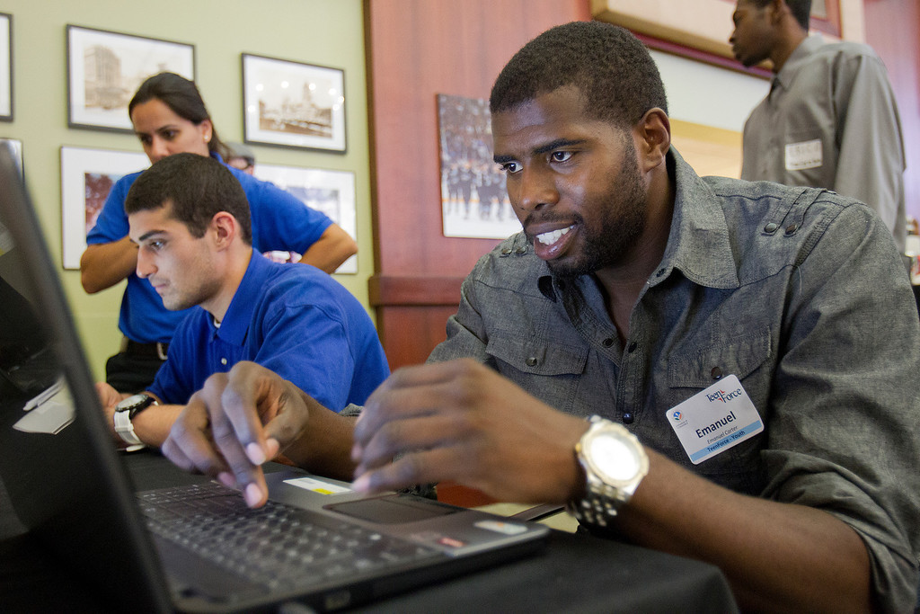 . From background left, Best Buy Hiring Coordinator Shirin Amiri, helps Michael McCarthy and Emmanuel Carter with the application process at a hiring fair  hosted by TeenForce and the San Jose Silicon Valley (SJSV) Chamber at the SJSV Chamber offices in San Jose, Calif. on Wednesday, June 26, 2013.  (LiPo Ching/Bay Area News Group)