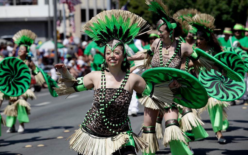 . Members of the Samba Mundial troupe dance along Marshall St. during the annual Fourth of July parade in Redwood City, Calif. on Thursday, July 4, 2013. Considered the largest Independence Day parade in Northern California, it is celebrating its 75th year. (Gary Reyes/Bay Area News Group)