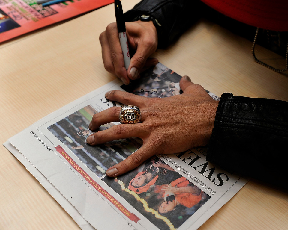 . Giants reliever Sergio Romo signs a newspaper from when the Giants won the World Series at a Marine Corps Reserve Toys for Tots event held at Kinders Meat and Deli on Wednesday, Dec. 12,  2012, in Pleasant Hill, Calif. (Susan Tripp Pollard/Staff)