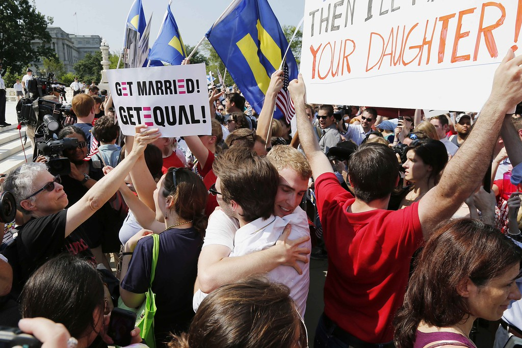 . Supporters of gay marriage embrace outside the Supreme Court in Washington, Wednesday, June 26, 2013, after the court cleared the way for same-sex marriage in California by holding that defenders of California\'s gay marriage ban did not have the right to appeal lower court rulings striking down the ban. (AP Photo/Charles Dharapak)