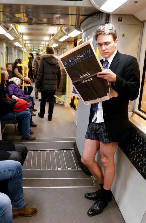 ". A man without his pants reads a newspaper in a subway train as he takes part at the ""No Pants Subway Ride\"" in Berlin January 13, 2013. The event, organised by Improv Everywhere, involves participants who strip down to their underwear as they go about their normal routine.         (REUTERS/Fabrizio Bensch GERMANY)  -"