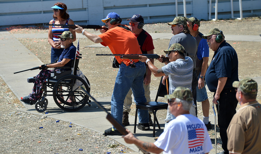 . Four veterans line up with their coaches and shoot at flying clay targets behind during the George Findly Memorial Disabled Veteran Trap Shoot at the Bay Point Rod and Gun Club in Concord, Calif., on Saturday, June 15, 2013.  Each vet was assigned a mentor/coach from the club and each got to shoot two sets of flying clay targets.  (Dan Rosenstrauch/Bay Area News Group)