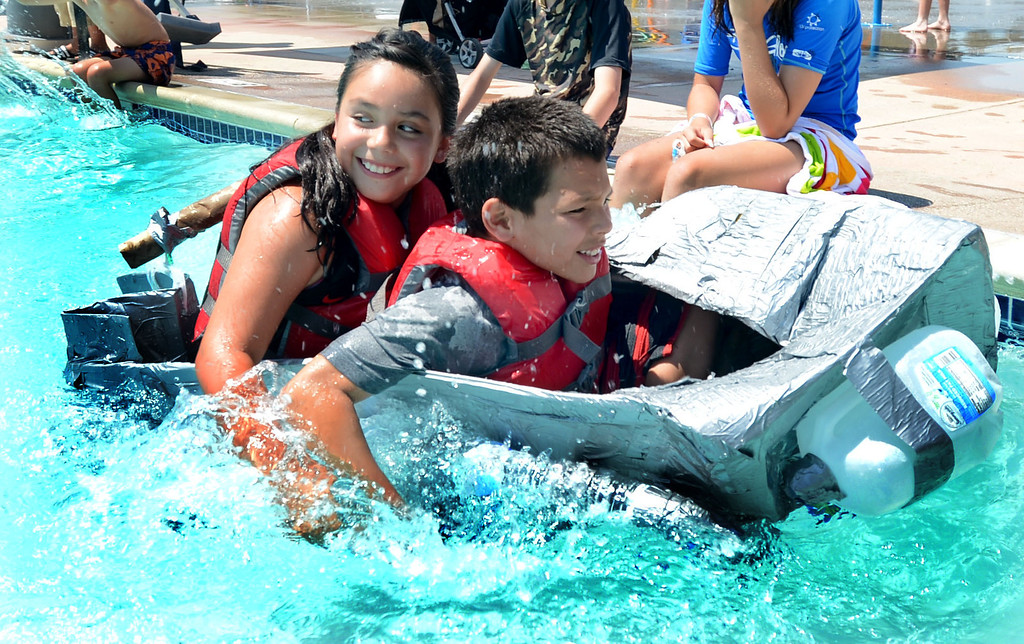 """. Nayeli Torres, 9, of Pittsburg, left, and Angelo Esposito, 8, of Concord, paddle across a pool in their watercraft named \""""Ship Awesome\"""" made of only cardboard, recyclables and duct tape during the Derby Day boat race held at Pleasant Hill Aquatic Park in Pleasant Hill, Calif., on Friday, July 19, 2013. (Doug Duran/Bay Area News Group)"""