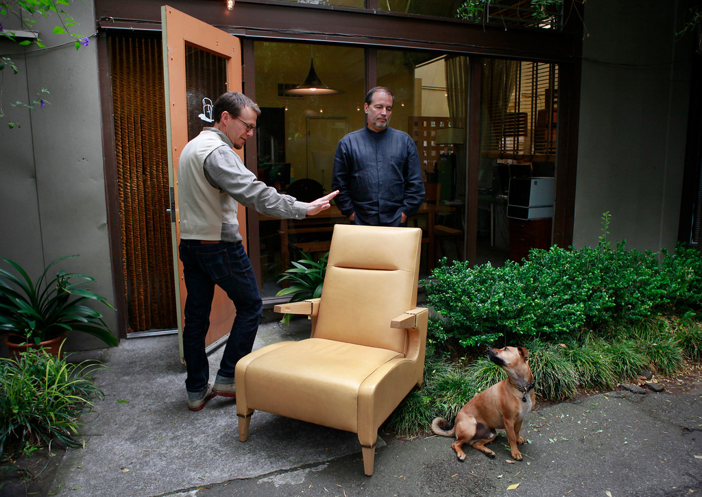 . Ted Boerner, left, and Frank Pontes founded Ted Boerner, Inc., 20 years ago as a San Francisco design studio dedicated to innovative, custom furniture. Now featured in showrooms around the country as well as their own NYC showroom, the pair show off their signature Lex Club Chair while giving orders to their dog Nemo at their offices Wednesday, July 11, 2013 in San Francisco, Calif. (Karl Mondon/Bay Area News Group)