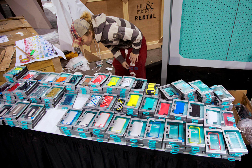 . Las Vegas Convention Center exhibit contractor Ruachelle Kulak searches through stacks of cell phone case while setting up a booth for X-Doria, Sunday, Jan. 6, 2013, in Las Vegas. X-Doria, a mobile accessories company, is one of thousands of consumer electronics exhibitors that will be showing products at the International Consumer Electronics Show, which opens on Tuesday and runs through Friday. (AP Photo/Julie Jacobson)