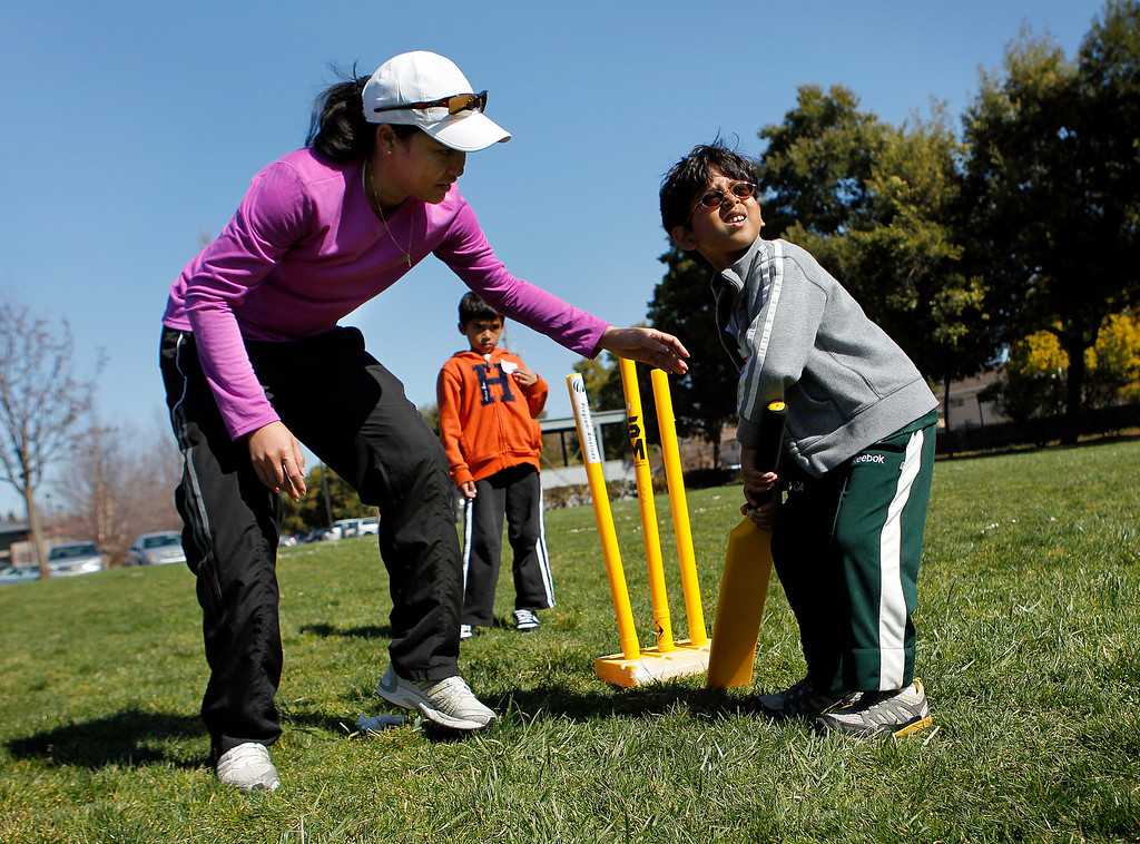 . At left, Nadia Gruny, who plays on the U.S. Women\'s Cricket Team, helps coach Satvik Rao, 6, right, with his batting at the cricket festival sponsored by the California Cricket Academy at the Cupertino Library Field\'s cricket pitch in Cupertino, Calif. on Saturday, March 9, 2013.  Boys and girls ages 5-13 were invited to attend and learn the basics of the game.  (LiPo Ching/Staff)