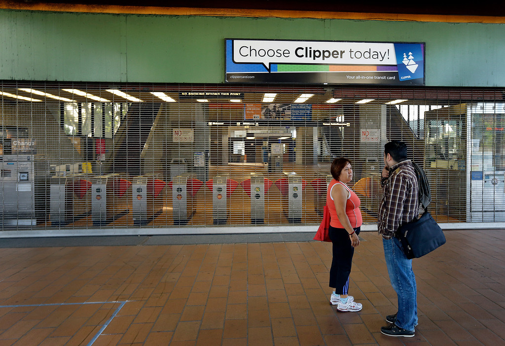 . A couple discuss a different way to travel upon learning that the Fruitvale BART station is closed due to a  strike Monday, July 1, 2013, in Oakland, Calif. (AP Photo/Ben Margot)