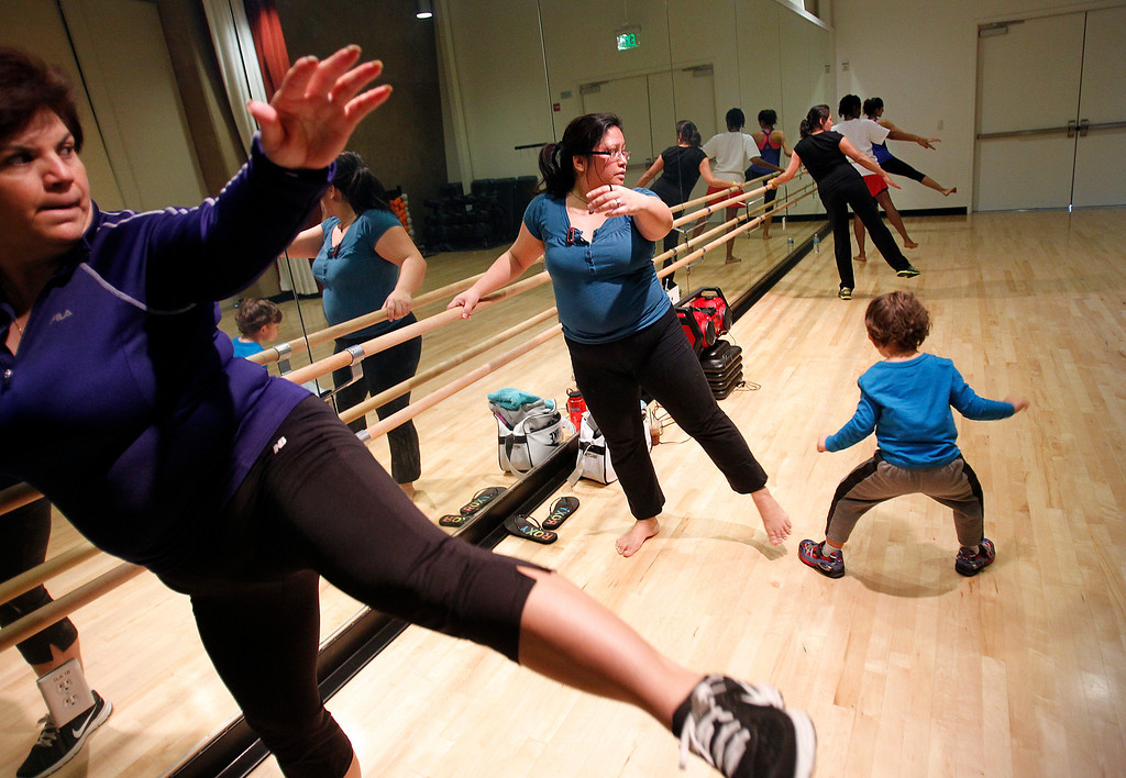 . From left, Maria Ramos, Babette Jugarap and her son Maddox Jugarap-Restani, 3, attend the Hot HUal Fitness Class at the Seven Trees Branch Library after its grand opening celebration, in San Jose, Calif. on Saturday, January 26, 2013.   (LiPo Ching/Staff)