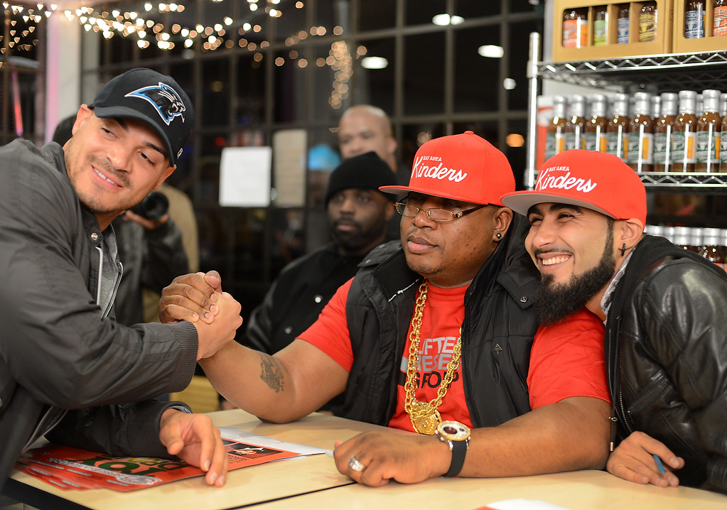 . Jarrod Cooper, of Danville, former safety with the Oakland Raiders, moves in close for a photograph with rapper E-40 and Giants reliever Sergio Romo at a Marine Corps Reserve Toys For Tots event at Kinder\'s Meats and Deli on Wednesday, Dec. 12,  2012, in Pleasant Hill, Calif. (Susan Tripp Pollard/Staff)