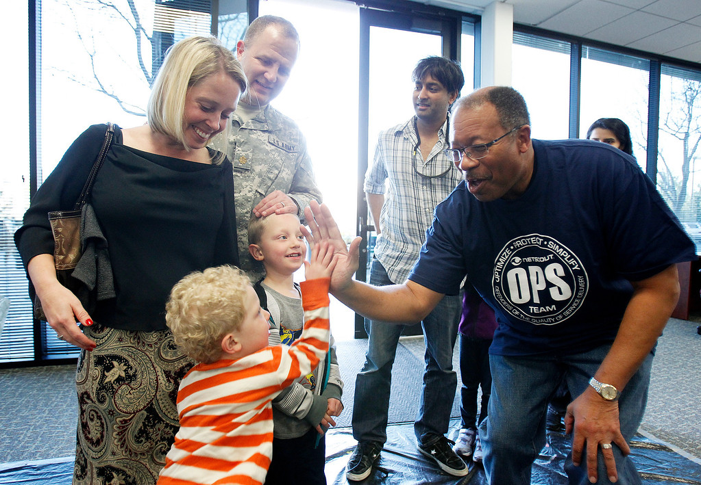 . From foreground left, Max Shearer, 2,  high fives NetScout Systems CIO Ken Boyd, as his mother Dawn Shearer, father U.S. Army Major Troy Shearer and brother Jacob Shearer, 5, look on at the NetScout offices in San Jose, Calif. on Thursday, Feb. 21, 2013.   (LiPo Ching/Staff)