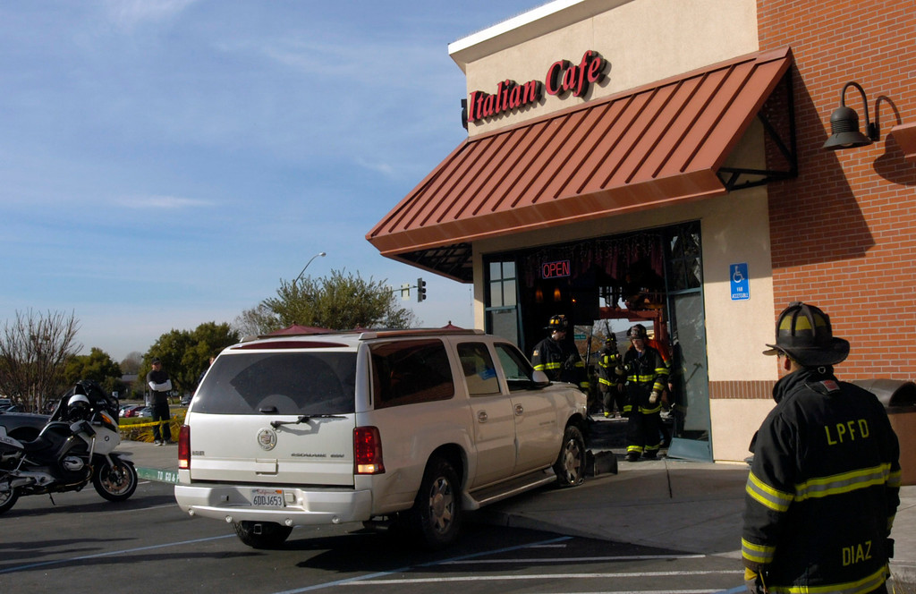 . A Cadillac Escalade SUV that was driven by accident through the Strings Italian Cafe during the lunch hour in Livermore, Calif., is backed out by an emergency responder on Monday, Jan. 7, 2013. One customer was taken to a hospital for treatment of injuries and several other people sustained minor injuries. (Cindi Christie/Staff)