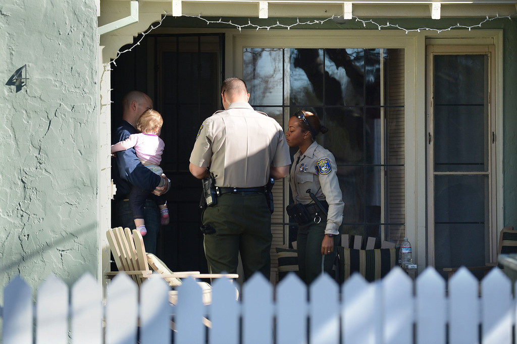 . Santa Clara County Sheriff\'s deputies Ryan Griep, center and Dessaure (she did not want her first name used), right, talk to a homeowner in an unincorporated portion of East San Jose, Calif. on Monday, Feb. 11, 2013. The Santa Clara County Sheriff\'s Office is increasing its efforts to take once lawfully owned firearms from those who can no longer own them due to more recent circumstances in their lives. Officers are attempting to make contact with these people and ask them to voluntarily turn over any firearms. The person they were looking for at this residence had moved. A monthly list of these people is put out by the Department of Justice. (Dan Honda/Staff)