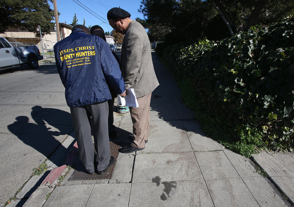 . Donald Paul Miller, right, and Ben Darden, of Allen Temple Baptist Church, pray with a woman who did not wish to be identified at a homicide scene on 94th Avenue and Hillside Street in Oakland, Calif. on Saturday, Jan. 12, 2013. Ken Harbin, 17, who lived nearby, was shot and killed there on Friday night about 8:15 p.m. according to Oakland police. There were four homicides in six hours on Friday in Oakland.  (Jane Tyska/Staff)