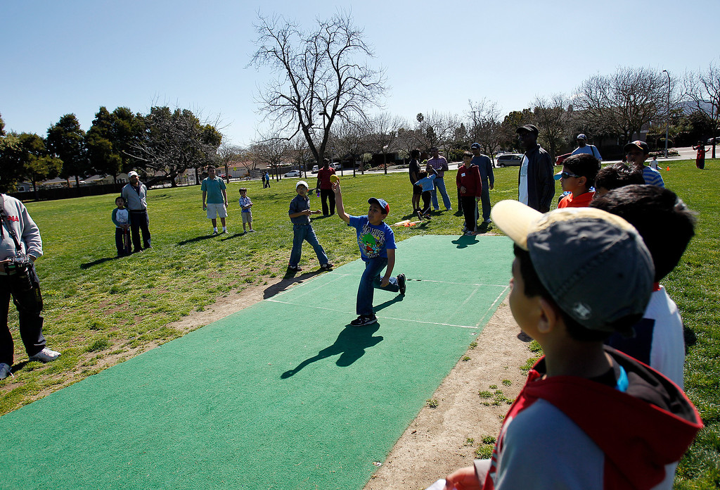 . At center, Anish Mankal, 9, practices bowling at the cricket festival sponsored by the California Cricket Academy at the Cupertino Library Field\'s cricket pitch in Cupertino, Calif. on Saturday, March 9, 2013.  Boys and girls ages 5-13 were invited to attend and learn the basics of the game.  (LiPo Ching/Staff)