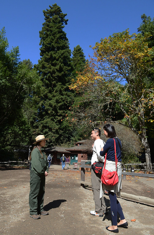 . Park ranger Michelle Armijo tells tourists Liu Ju, left, and Ning Quong, of Guangzhou, China, that  Muir Woods National Monument is closed due to the federal government shutdown in Mill Valley, Calif. on Tuesday, Oct. 1,  2013. Rangers allowed those who parked down the road to walk as far as the entrance to take a quick look before leaving. (Alan Dep/Marin Independent Journal)