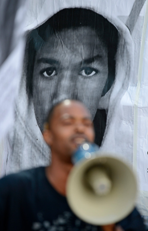 . A protester uses a bullhorn to speak to the crowd as a poster of Trayvon Parker is raised behind him at Frank Ogawa Plaza in Oakland, Calif., on Sunday, July 14, 2013. A jury ruled Saturday that defendant George Zimmerman has been found not guilty in the shooting death of Trayvon Martin. (Jose Carlos Fajardo/Bay Area News Group)