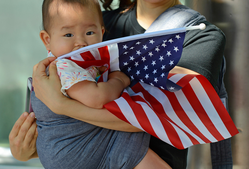 . Kokoro Motegi, of Orinda, holds her daughter Sophie, 9 months old, as they watch the 30th anniversary Lamorinda Fourth of July parade and celebration on Thursday, July 4, 2013. (Jose Carlos Fajardo/Bay Area News Group)