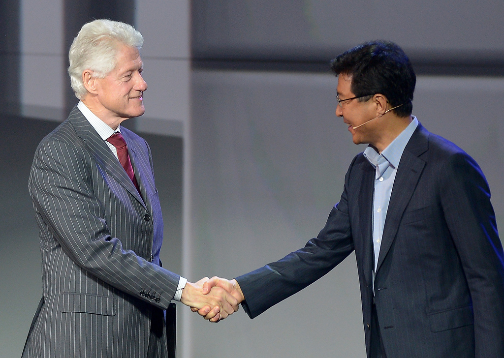 . Former US President Bill Clinton is thanked by Dr. Stephen Woo ,the president of Samsung\'s Electronic Device Solutions,during Samsung\'s press conference at the 2013 International CES at the Las Vegas Convention Center on January 9, 2013 in Las Vegas, Nevada. (JOE KLAMAR/AFP/Getty Images)