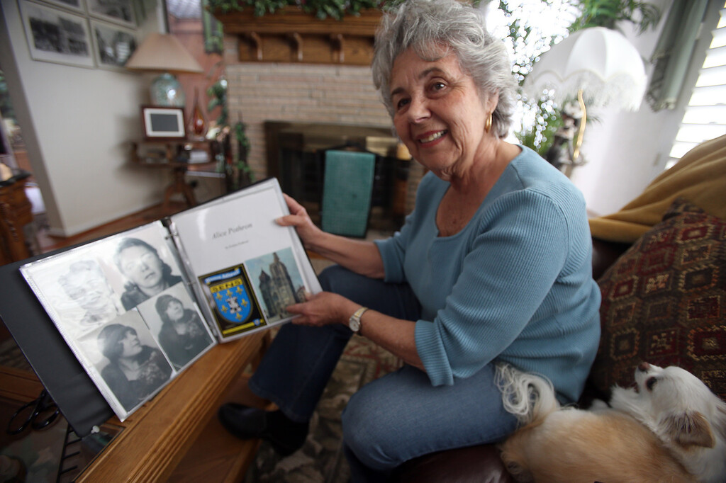 . Evelyne Pothron looks through a family scrapbook at her home in Alameda, Calif., on Thursday, Jan. 24, 2013. (Jane Tyska/Staff)