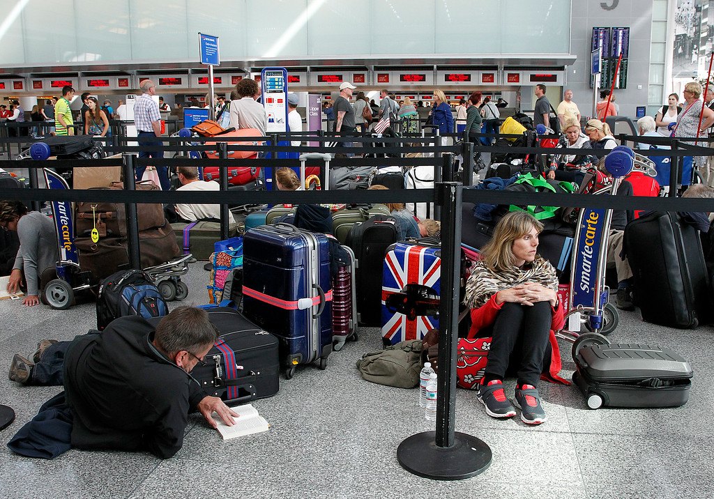 . Passengers wait in line at the British Airways International check-in counter after Asiana Airlines Flight 214, arriving from Seoul, South Korea, crashed at San Francisco International Airport (SFO), San Francisco, Calif. on Saturday July 6, 2013.  All flights from SFO were delayed after the crash. (LiPo Ching /Bay Area News Group)